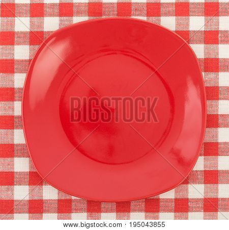 Stylish Red Plate On A White And Red Checkered Tablecloth. Top View, Close Up.