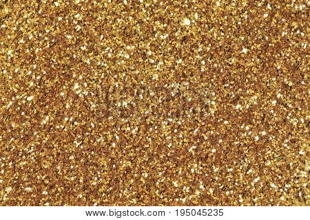 Background filled with shiny gold glitter. High res macro photo.
