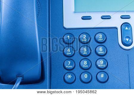 Modern IP digital phone details. Blue toned.