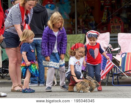 Alameda CA - July 04 2017: The Alameda 4th of July Parade is one of the largest and longest Independence Day parade in the nation. Unidentified persons waiting for the parade to start pet bunny