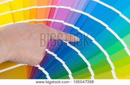 The person with a finger shows to the selected color in the palette for paint tinting. Colored catalog fan. The concept of choosing interior design