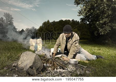 Vagabond young man wake up in park near illegal fire place