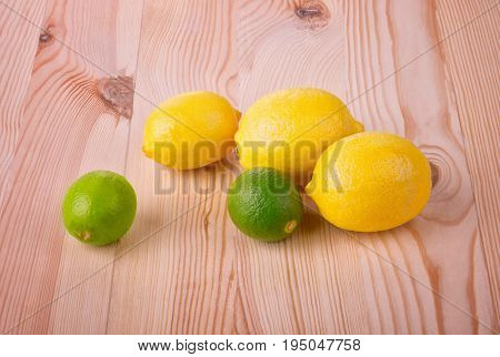 Three juicy, ripe and yellow lemons and two bright green limes. Tropic fruit. Lemons and limes on a light wooden table. Citrus fruits. Vitamins.