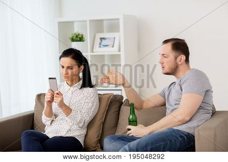 people, relationship difficulties and conflict concept - man drinking beer and woman with smartphone having argument at home