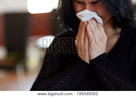 people, grief and mourning concept - close up of crying woman with wipe at funeral in church