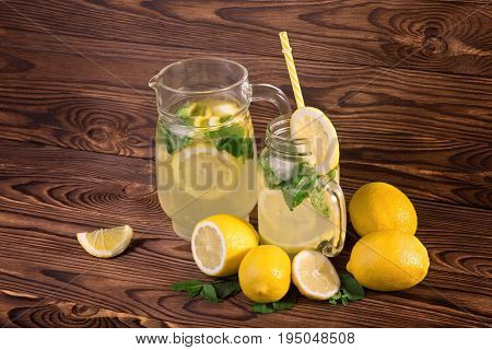A pitcher and a glass of refreshing mojito from tasty mint and ripe lemons, and crushed ice on a dark wooden background. Glasses of lemons cocktails on wooden table with a green mint and fresh lemons