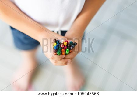 Closeup of child's hands with lots of colorful wax crayons pencils. Kid preparing school and nursery equipment and student stuff. Back to school. Education, school, learning concept.
