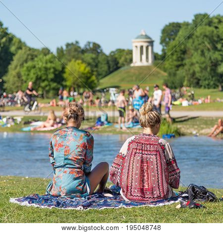 People enjoying the summer, sunbathing, swimming in river Izar and relaxing on green of the Englischer Garten in Munich, Germany on a sunny summer holiday day.