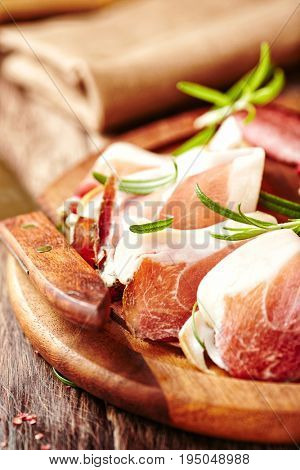 Cured and dried ham with rosemary on a chopping board