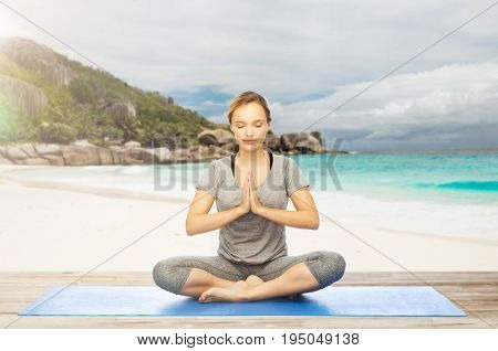 fitness, people and healthy lifestyle concept - woman doing yoga meditation in lotus pose on mat over exotic tropical beach background