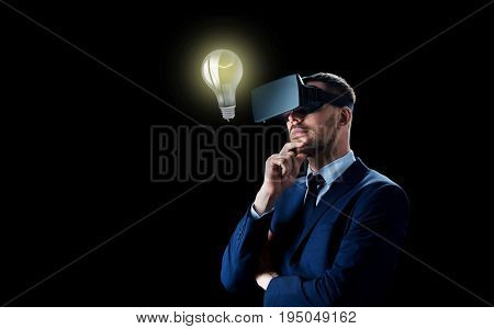business, people, startup idea, augmented reality and modern technology concept - businessman in virtual headset looking at lightbulb over black background