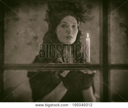 Worn Wet Plate Photo Of Victorian Woman In Black Dress Standing Behind Window Holding Candlestick.