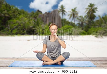 fitness, meditation and healthy lifestyle concept - woman doing yoga breathing exercise in lotus pose on mat over exotic tropical beach background