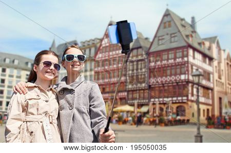 tourism, childhood and travel concept - happy girls taking picture with smartphone on selfie stick over frankfurt am main city street background