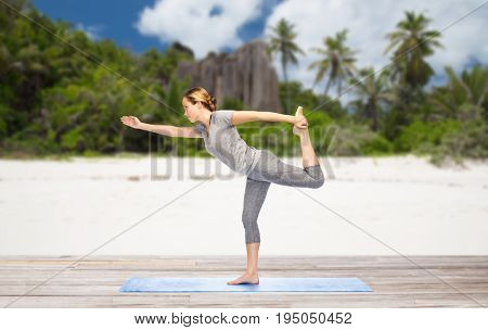 fitness, sport and people concept - woman doing yoga in lord of the dance pose on mat over exotic tropical beach background