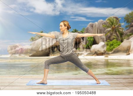 fitness, sport and people concept - woman doing yoga warrior pose on mat over exotic tropical beach background
