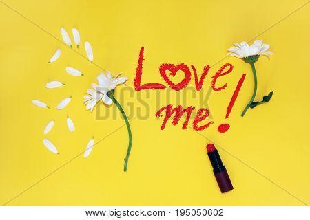 The phrase love me written by lipstick.