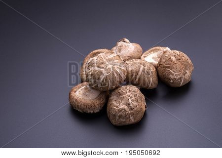 Shiitake mushrooms on a black table background.