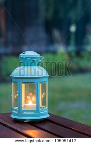 Scented candle in a pretty lantern with outdoor green background