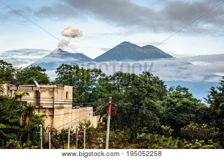 Smoke spurts from erupting Fuego volcano next to Acatenango volcano just after dawn near Antigua, Guatemala, Central America