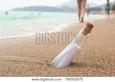 message in a glass bottle on the beach. People bathe in the sea on the waves and walk along the beach. Found a note on salvation please help.