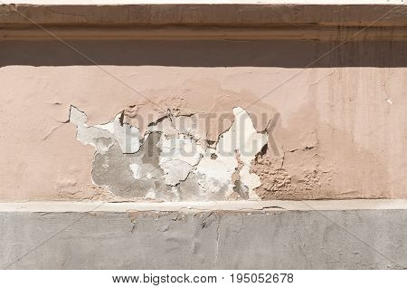 Peeling mortar - plaster damaged of moisture on facade of old house.