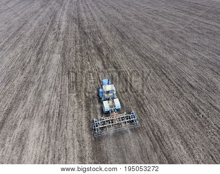 Cultivation Of Soil For The Sowing Of Cereals. Tractor Plows The Soil On The Field