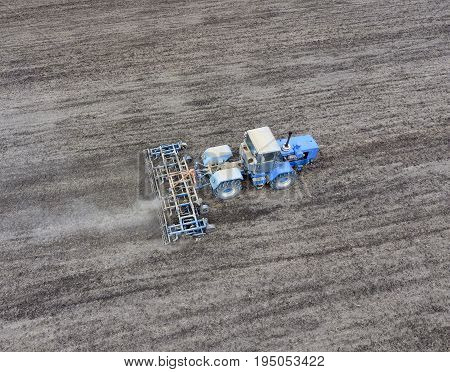 The Tractor Plows The Field. Under Sowing, The Soil Is Loosened On The Field.