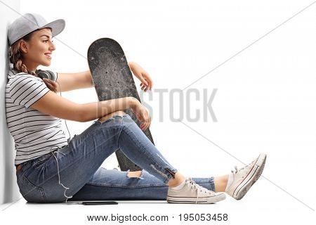 Teenage girl with a skateboard sitting on the floor and leaning against a wall isolated on white background