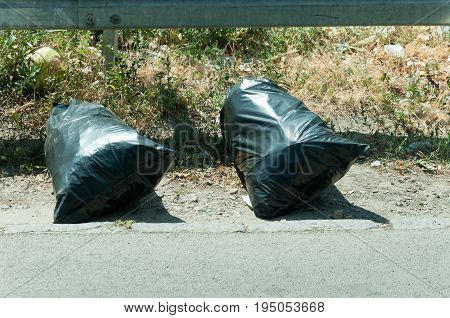 Two plastic black garbage bags thrown on the street. Litter.