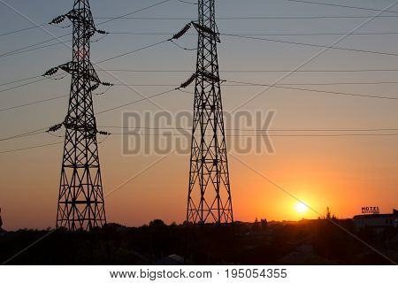 High voltage transmission power line silhouette on sunset