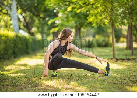 A sportswoman is doing exercise. A woman with wonderful and amazing long light brown hair is doing stretching in the green park. The good-looking lady is dressed in a black top, black leggings.
