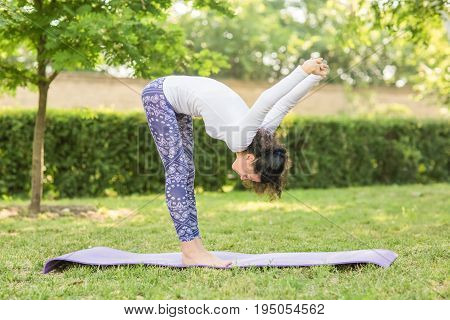 The athletic woman practising yoga pose in the park with a lot of trees and bushes. The meditation has good benefits for health. A charming lady in a white sweater and blue leggings is doing yoga outdoor.