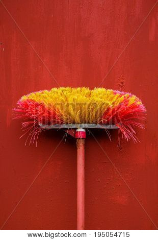 Old red broom with metal hand grip against red wall