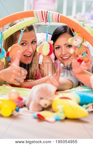 Soon-to-be moms testing baby toys for neonates