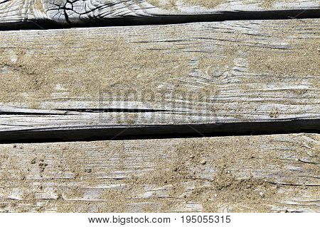 Close up of wooden jetty with sand