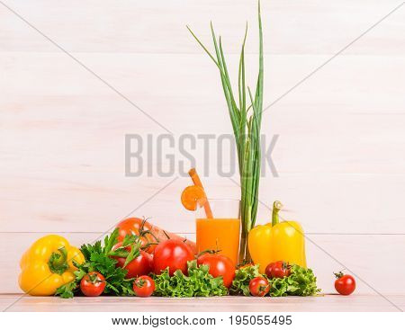 Various healthful veggies on a light wooden table. Vegetables on a bright background. Organized tasteful lettuce, tomatoes, pepper. Delicious orange juice in a glass.