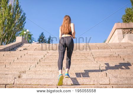 A happy and ideal girl with beautiful fluffy long blond hair is climbing up the stairs. A good-looking lady is dressed in black leggings, a black top and blue trainers with yellow accents outdoor.