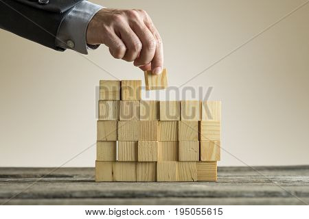 Businessman Building A Structure With Wooden Cubes On Table Surface