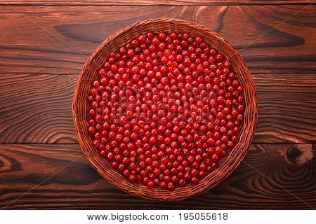 Close-up nutritious red currant on a bright wooden background. Delicious red berries in a light brown basket. Healthful organic berries on a dark brown table.