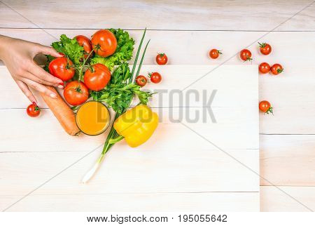 Close-up food ingredients on a light background. Tasteful vegetables on a spacious wooden table. A hand holding a fresh red tomato, laying next to the lettuce. A glass full of orange juice.