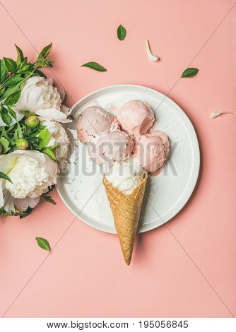 Flatlay of pastel pink strawberry and coconut ice cream scoops, sweet cones on white plate and white peonies over pastel pink background, top view, copy space, vertical composition