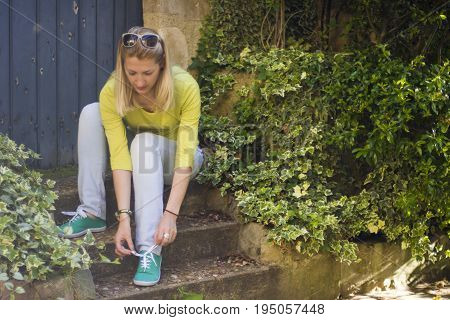 Young blonde girl ties up shoelaces on green sneakers