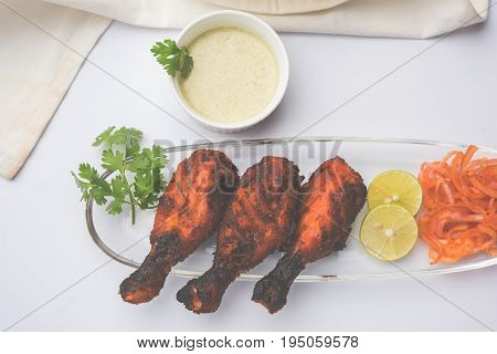 Chicken Tangri kabab or kebab - three Chicken leg pieces marinated with red sauce then grilled and served with salad. It can be served with green chutney