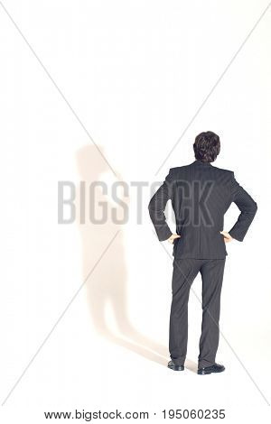 Full length rear view of a businessman with hands on hips arguing his shadow against white background