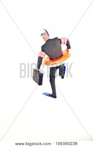Rear view of a businessman in flippers; inflatable rubber ring; snorkel and goggles holding briefcase against white background