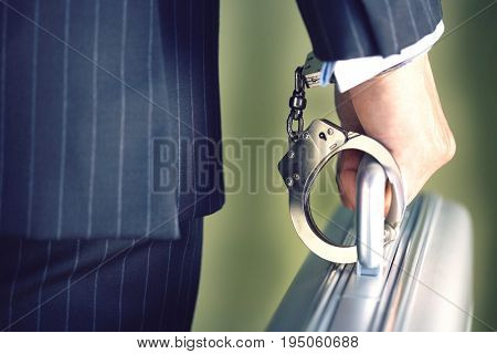 Closeup midsection of a businessman handcuffed to briefcase against green background