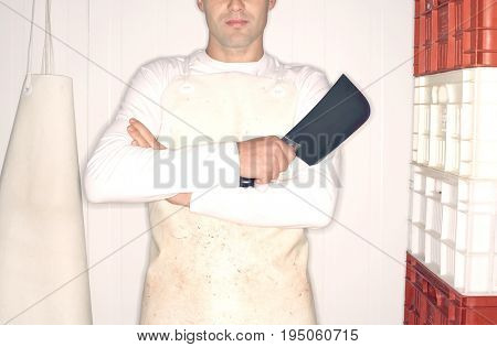 Closeup midsection of a butcher holding cleaver with arms crossed