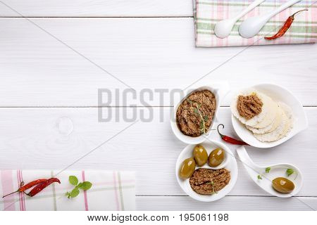 Tapenade - spicy olive paste made from green olives and red hot chilli pepper. On white wooden table. Copy space. Top view.
