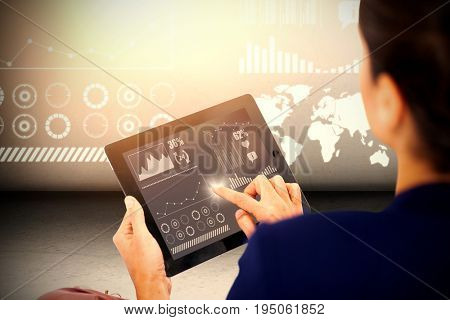 Businesswoman working on digital tablet over white background against grey room